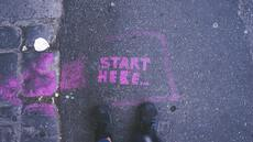 """start here"" written on the ground with pink chalk"