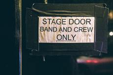"door sign with ""stage door band and crew only"" written on it"