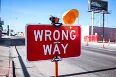 Wrong way sign, written in white on a red rectangle with an orange light
